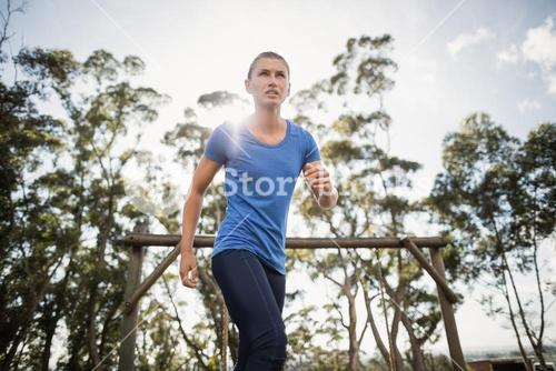 Fit woman running through obstacle course