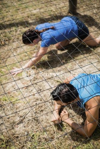 Fit man and woman crawling under the net during obstacle course
