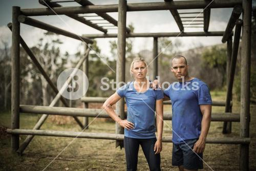 Fit woman and man standing against monkey bars during obstacle course