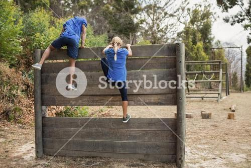 Fit man and woman climbing over wooden wall during obstacle course