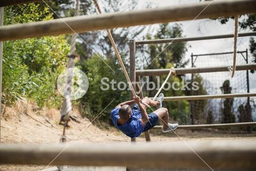 Man crossing the rope during obstacle course