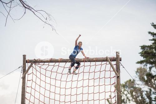 Fit woman with hand raised celebrating success during obstacle course