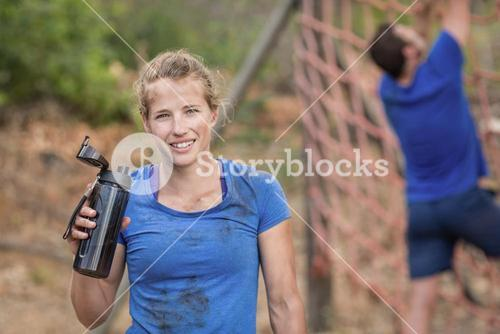 Portrait of woman holding water bottle during obstacle course