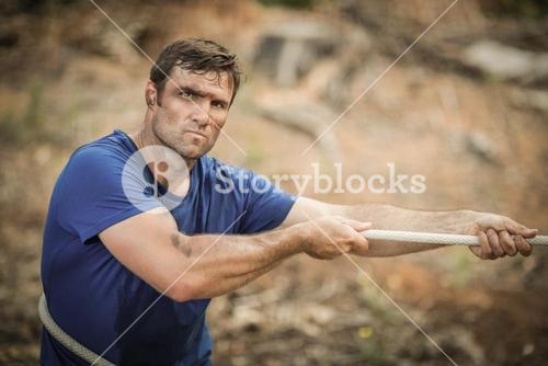 Man playing tug of war during obstacle course