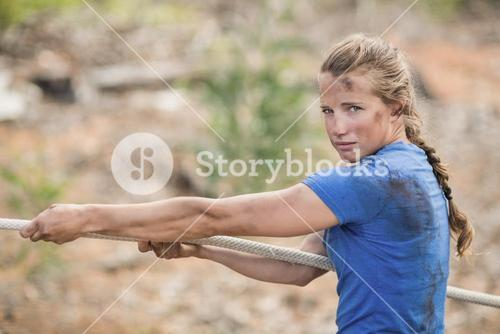 Woman playing tug of war during obstacle course
