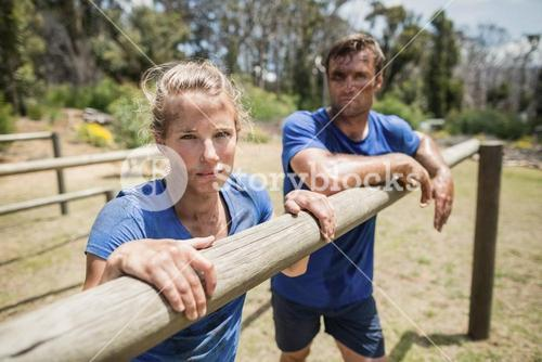 Tired man and woman leaning on a hurdle during obstacle course