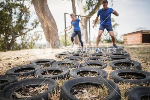 Man and woman running over the tyre during obstacle course