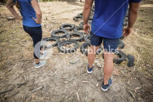 Man and woman standing near tyre during obstacle course