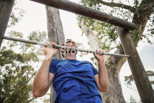 Fit man performing pull-ups on bar during obstacle course