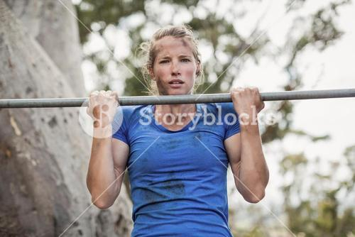 Fit woman performing pull-ups on bar during obstacle course