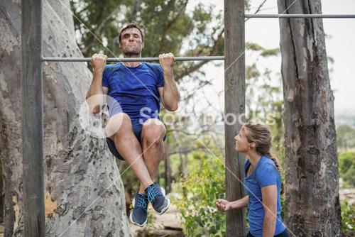 Fit man and woman performing pull-ups on bar during obstacle course