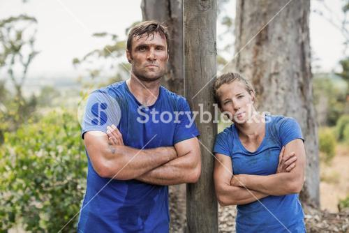 Tired man and woman standing with arms crossed during obstacle course