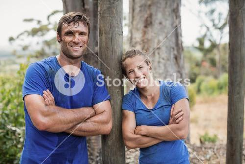 Smiling man and woman standing with arms crossed during obstacle course