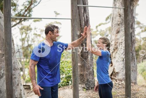 Smiling man and woman giving high five during obstacle course