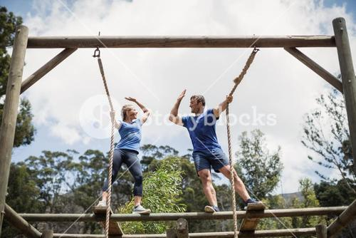 Fit man and woman giving high five during obstacle course