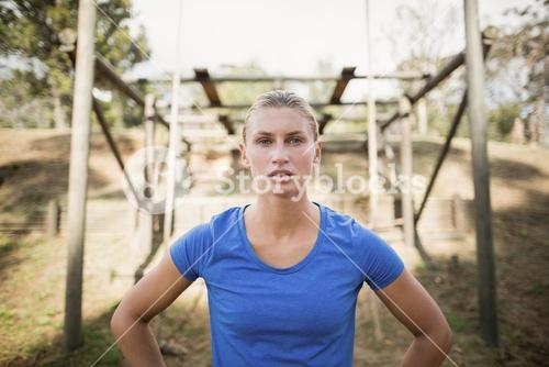 Portrait of fit woman standing with hands on hip during obstacle course