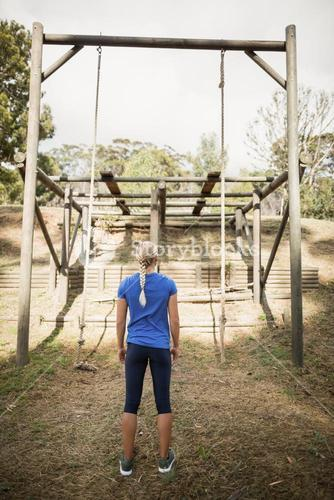 Rear view of fit woman looking at rope during obstacle course