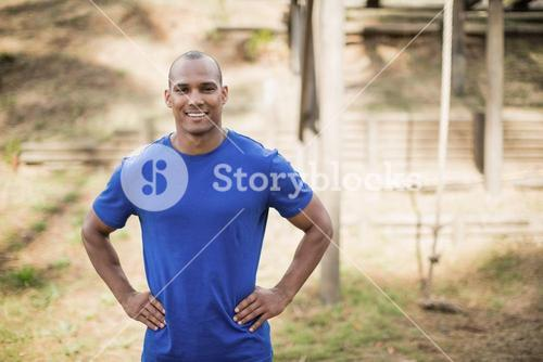 Portrait of fit man standing with hands on hip during obstacle course