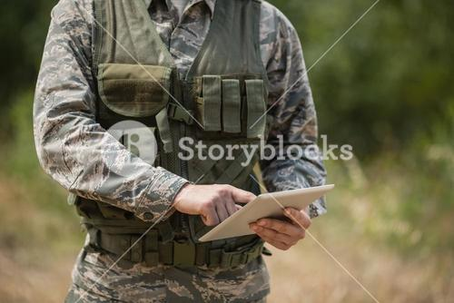 Mid section of military soldier using digital tablet
