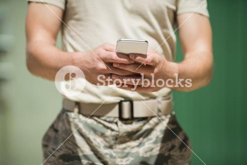 Mid section of military soldier using mobile phone