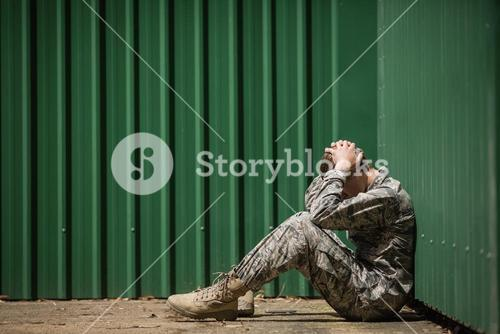 Frustrated military soldier sitting with hands on head