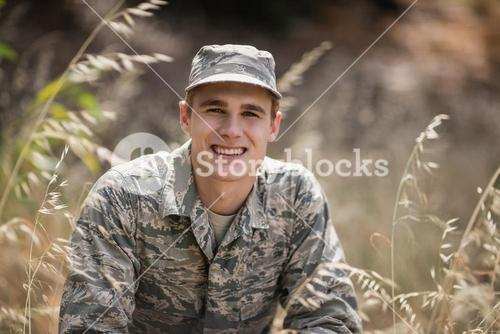 Portrait of happy military soldier crouching in grass
