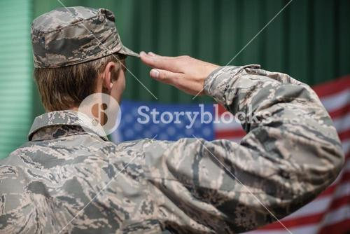 Rear view of military soldier giving salute to american flag