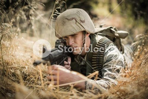 Military soldier aiming with a rifle