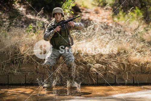 Military soldier with rifle jumping in water