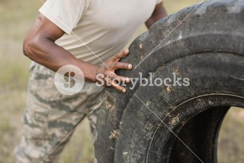 Mid section of military soldiers exercising with tyre
