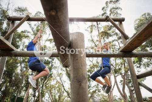 Fit man and woman climbing rope during obstacle course