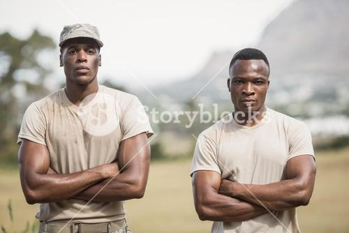 Military soldiers standing with arms crossed during obstacle course