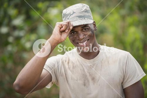 Portrait of happy military soldier holding his cap