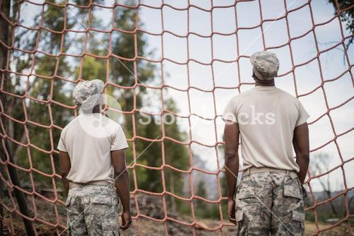 Military soldiers looking at net during obstacle course