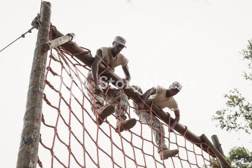 Military soldiers climbing a net during obstacle course