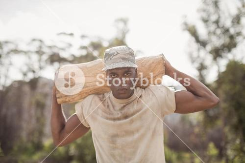 Military soldier carrying a tree log during obstacle course