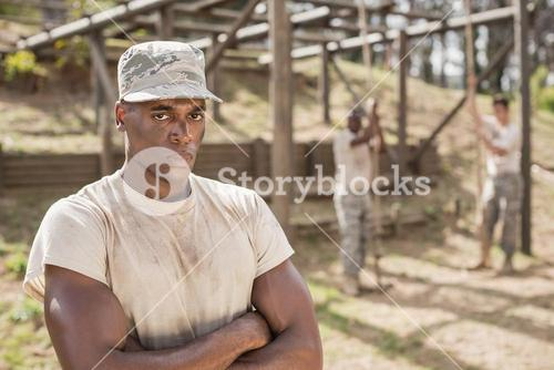 Military man standing with arms crossed during obstacle course in boot camp
