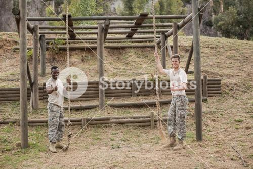 Military soldiers showing thumbs while holding rope during boot camp training