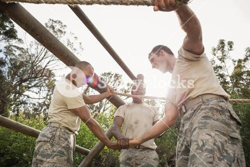 Military soldiers with hands stacked during obstacle training
