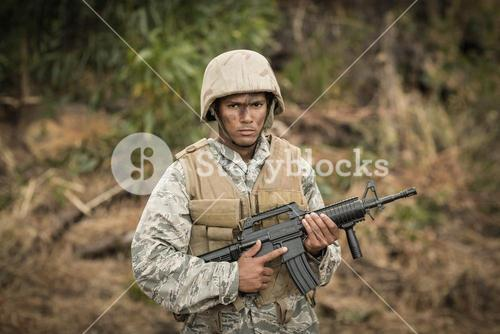 Military soldier guarding with a rifle in a boot camp