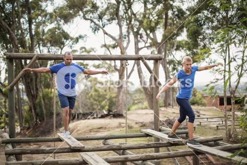 Fit man and woman during obstacle course training
