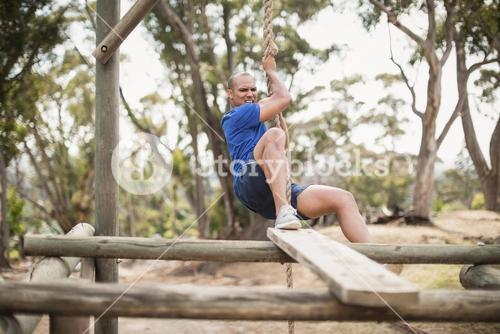 Fit man climbing a rope during obstacle course