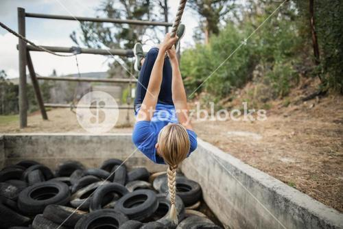 Woman climbing rope during obstacle course training