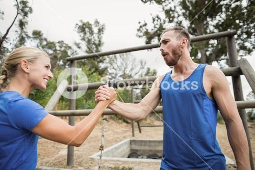Fit man and woman greetings during obstacle course