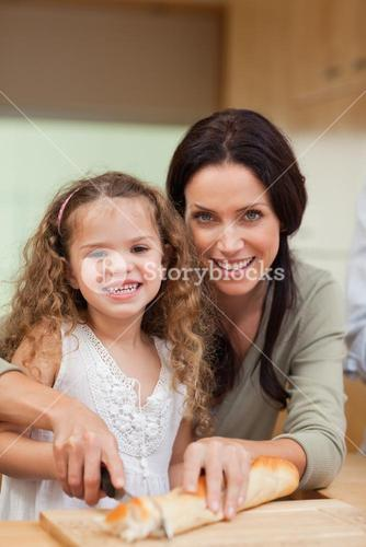 Mother and daughter slicing bread