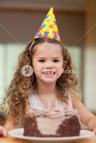 Girl with a slice of cake in front of her