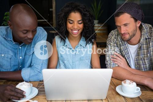 Smiling friends using laptop at table in coffee house