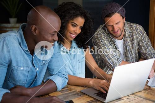 Happy friends using laptop in coffee shop
