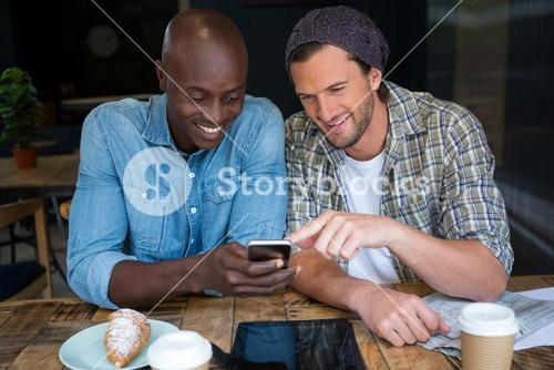 Happy male friends using mobile phone in coffee house