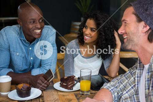 Friends talking at table in coffee house